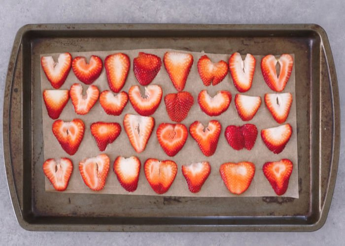 Sliced berries on baking sheet