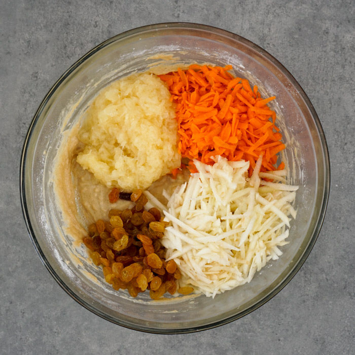 Carrots, pineapple, apple, and raisins added to the mixing bowl