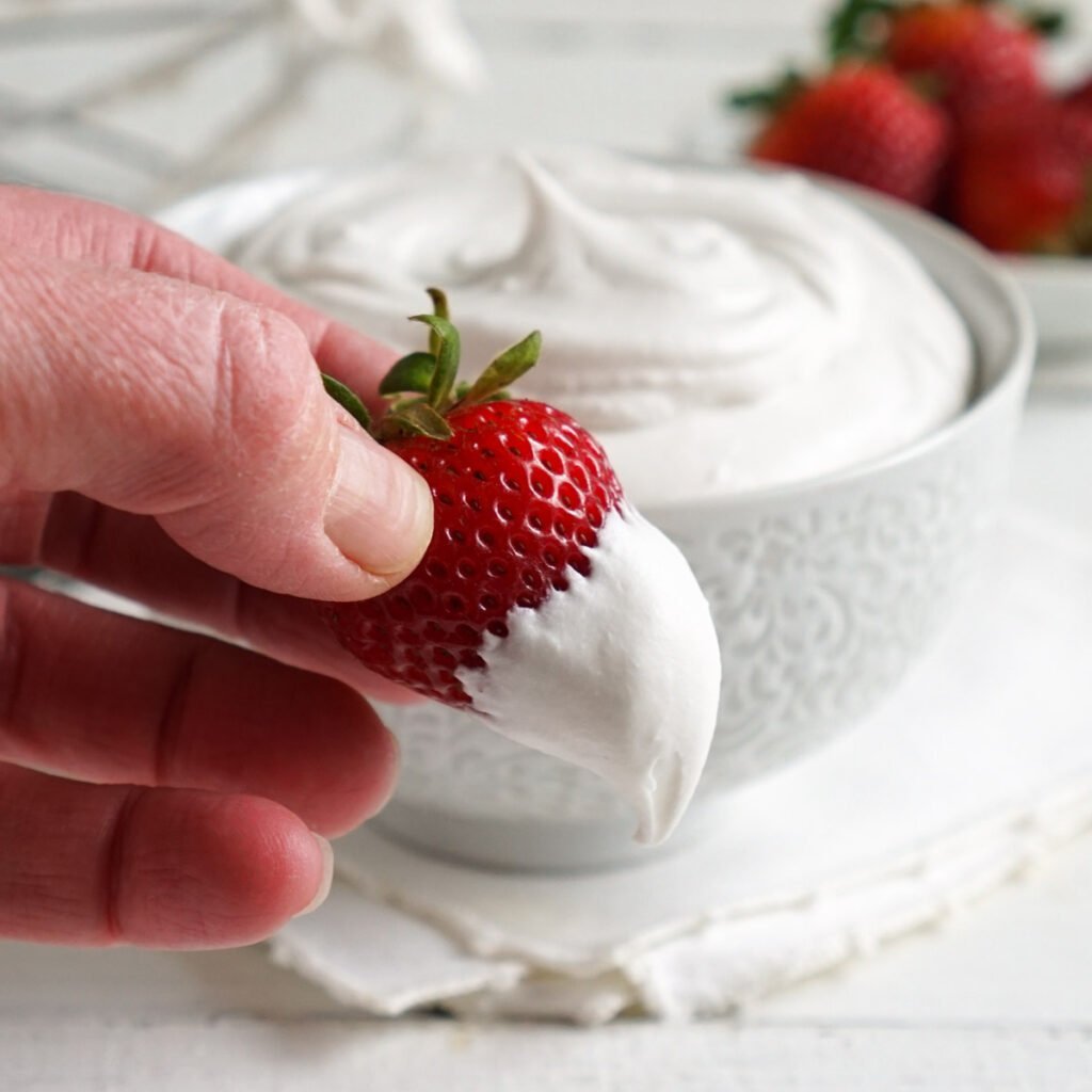 Strawberry dipped in vegan whipped cream